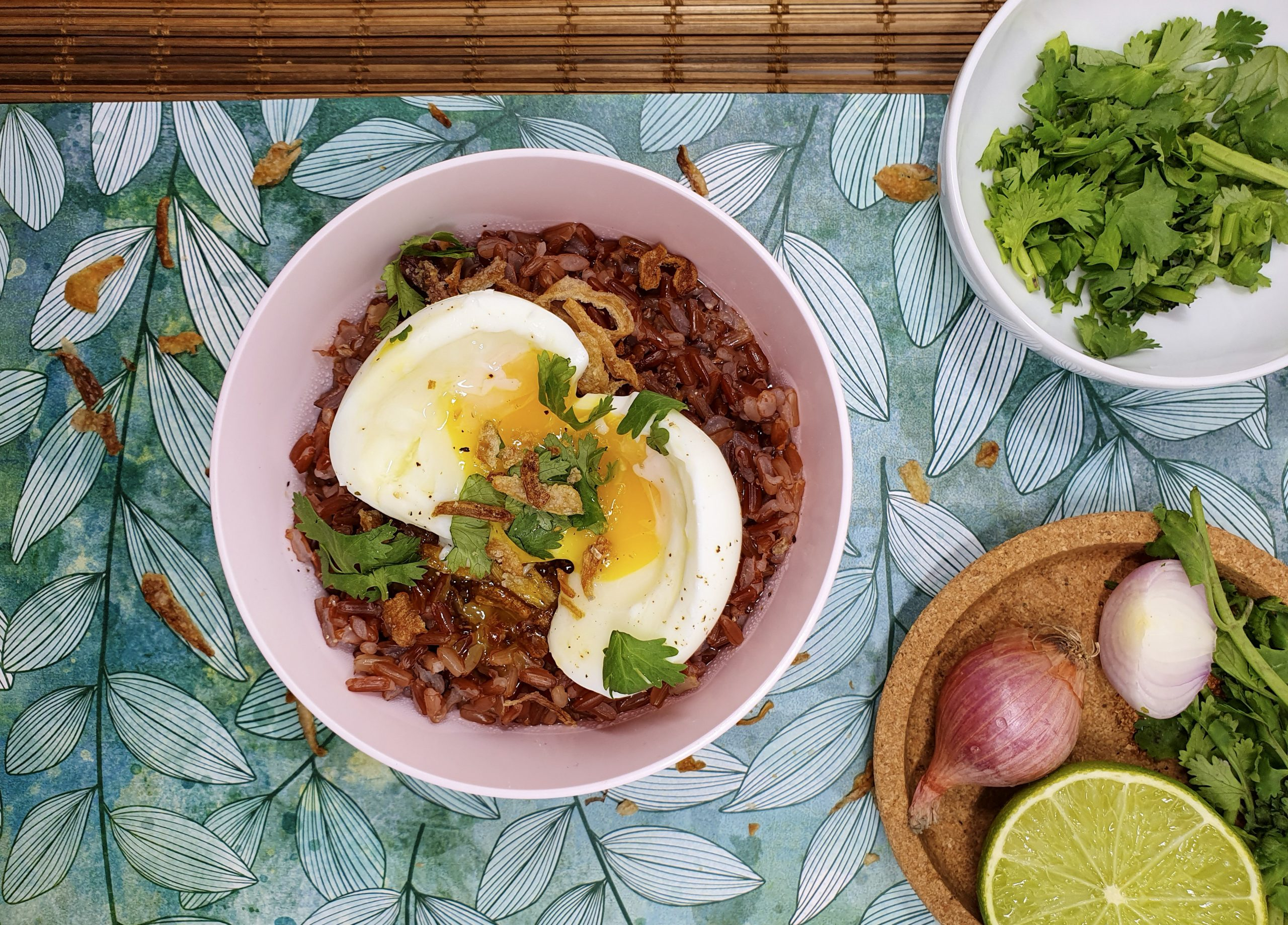 Bowl with red rice porridge with an egg and a plate with lemon, onion and parsley