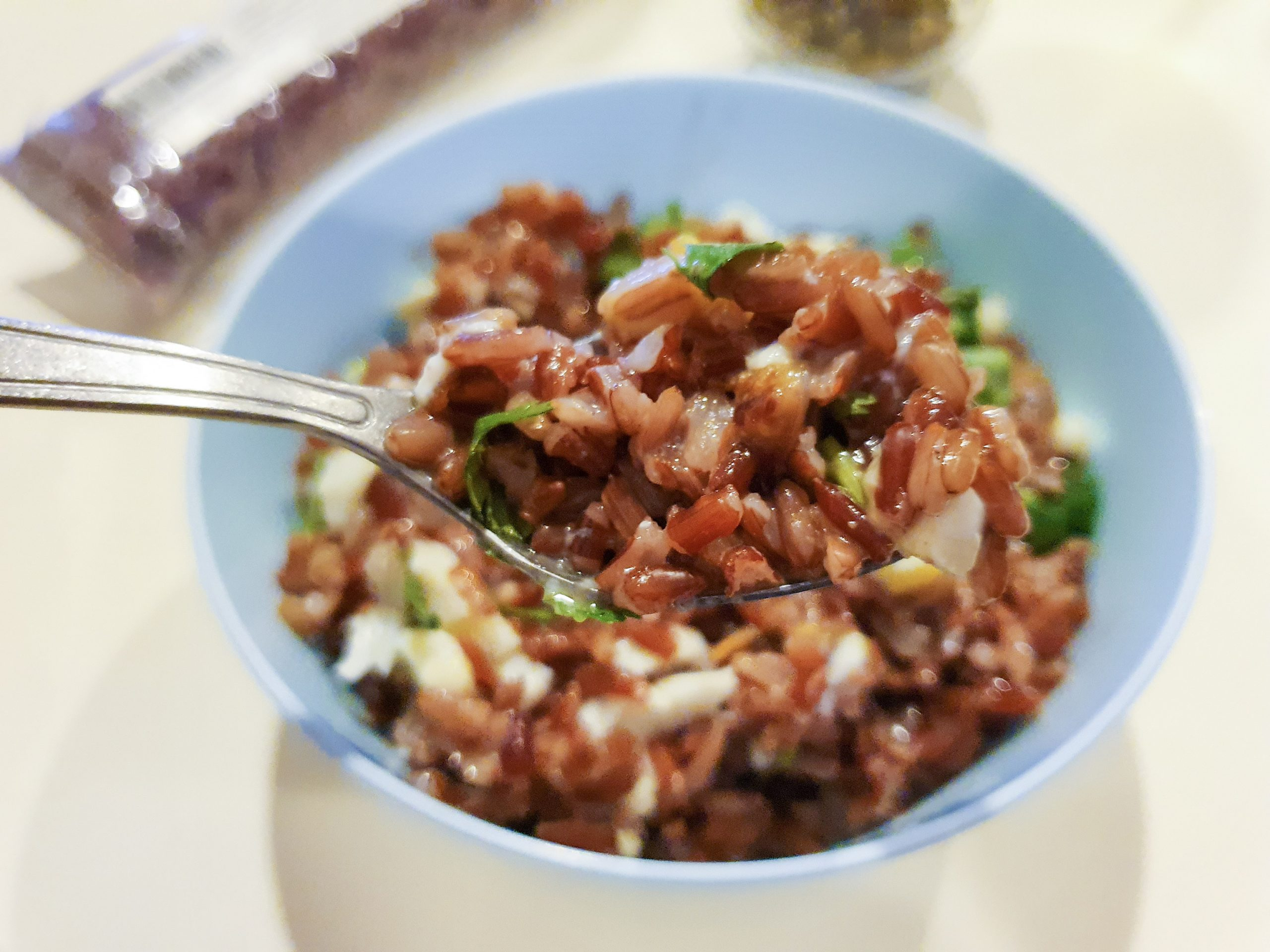 Close up image of a spoonful of Red rice porridge