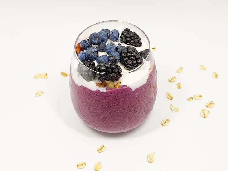 Glass with Blueberry oatmeal smoothie topped with granola and coconut cream